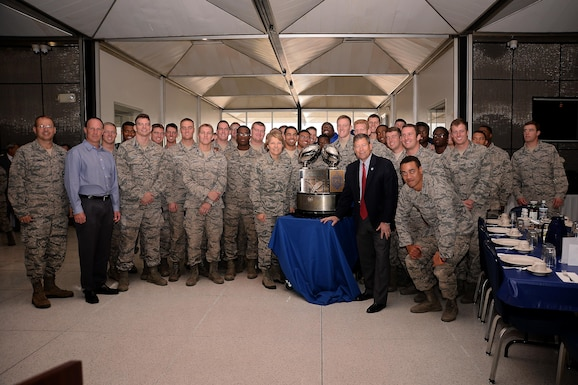 Lt. Gen. Michelle Johnson (center left), the superintendent of the U.S. Air Force Academy, and Dr. Jim Knowlton, the director of the Academy's Athletics Department (center right), stand besides the Commander-in-Chief's Trophy Nov. 17, 2017, in Mitchell Hall.  Johnson presented the trophy to the Cadet Wing from the Staff Tower during a long round of applause from cadets. Standing with Johnson and Knowlton are Falcon Football head coach Troy Calhoun, members of the Air Force Falcons, and Brig. Gen. Stephen Williams, the commander of the Cadet Wing. (U.S. Air Force photo/Darcie Ibidapo)