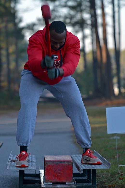 A U.S. Airman assigned to the 20th Fighter Wing hits a block with a hammer during a Firefighter Combat Challenge 5K Run at Shaw Air Force Base, S.C., Nov. 18, 2016. Airmen from various squadrons worked together in teams to complete obstacles created to test their physical endurance as well as build camaraderie following the conclusion of operational readiness exercise Weasel Victory 17-03. (U.S. Air Force photo by Airman 1st Class Christopher Maldonado)