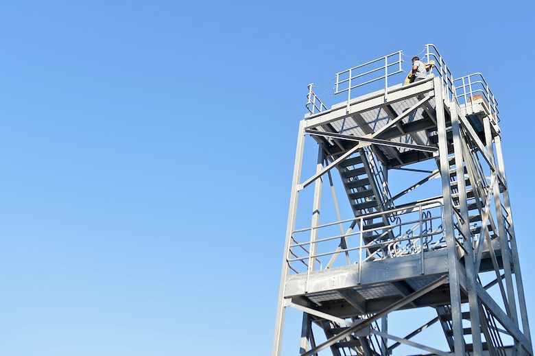 A U.S. Airman assigned to the 20th Aerospace Medicine Squadron carries a hose to the top of a tower during a Firefighter Combat Challenge 5K Run at Shaw Air Force Base, S.C., Nov. 18, 2016. Participants in the event overcame obstacles to include: mannequin transportation, operating fire hoses and tractor tire flips throughout the run. (U.S. Air Force photo by Airman 1st Class Christopher Maldonado)