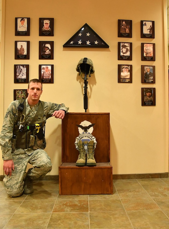 Senior Airman Zachary Clapper, 319th Security Forces Squadron patrolman, kneels in front of a security forces memorial on Grand Forks Air Force Base, N.D., Nov. 18, 2016. Clapper received the Airman 1st Class Elizabeth Jacobson Award for Expeditionary Excellence, an award named after the first defender killed in the line of duty in support of Operation Iraqi Freedom. (U.S. Air Force photo by Airman 1st Class Elijaih Tiggs)