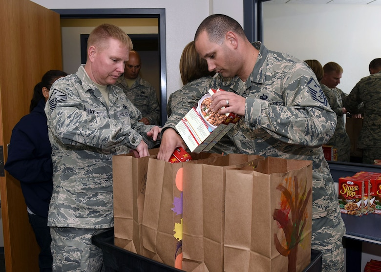 Master Sgt. James Taylor and Master Sgt. Kyle Fenimore, 30th Logistics Readiness Squadron First Sergeants, prepare turkey baskets for Airmen as part of Vandenberg's First Sergeant's Council annual Turkey Basket Drive, Nov. 18, 2016, Vandenberg Air Force Base, Calif. The Turkey Basket Drive is a nonprofit organization dedicated to provide a Thanksgiving meal to Vandenberg families in need. (U.S. Air Force photo by Senior Airman Kyla Gifford/Released)