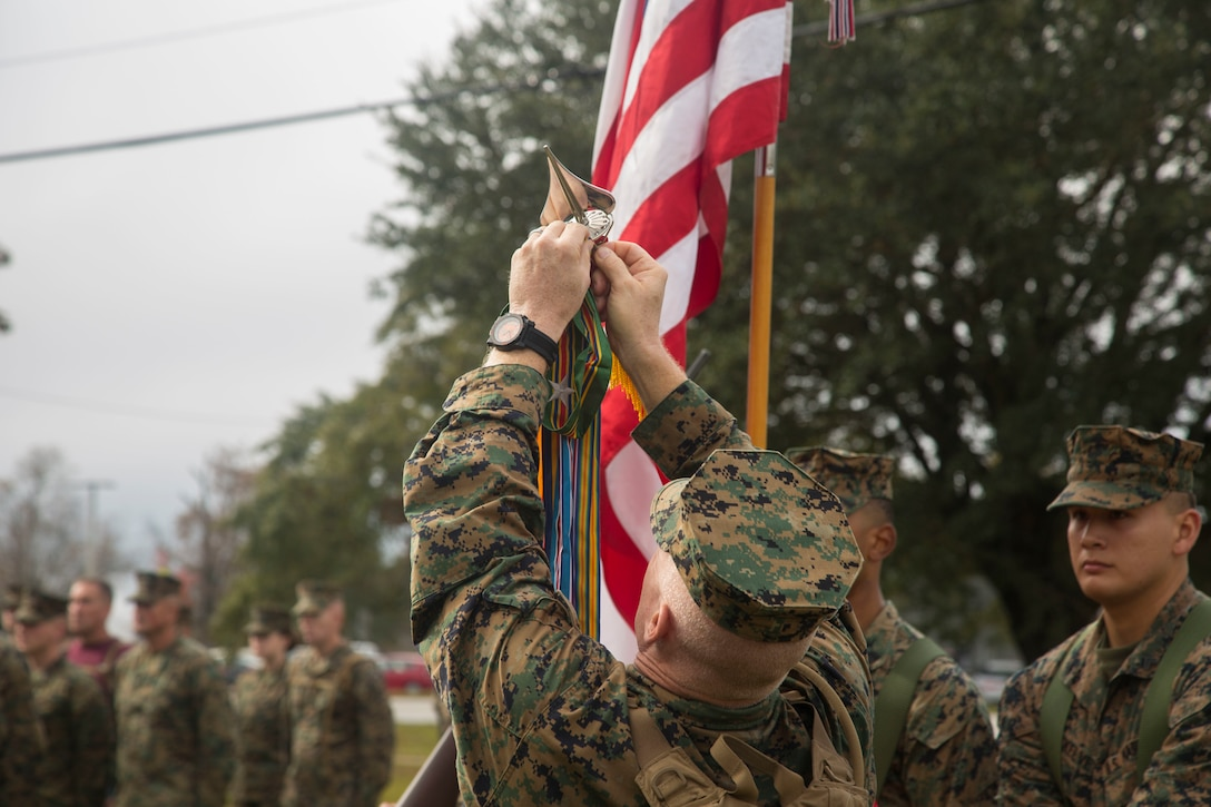 U.S. Marine Corps Brig. Gen. Thomas Weidley, commanding general, Marine Corps Installations East, Marine Corps Base Camp Lejeune (MCIEAST, MCB CAMLEJ) attaches a Meritorious Unit Commendation streamer to the colors during ceremony on Camp Lejeune, Nov. 14, 2016. Headquarters and Support Battalion, MCIEAST, MCB CAMLEJ conducted a 7.5 mile motivational and educational hike in recognition of the 75th anniversary of Camp Lejeune.
