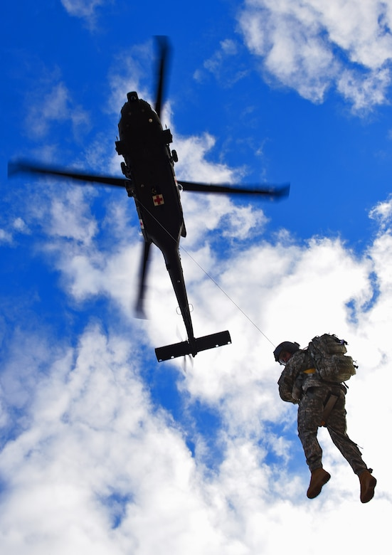 A soldier from the South Dakota National Guard's Company C, 1st Battalion, 189th Aviation Regiment, descends from an UH60 Blackhawk helicopter during Exercise Combat Raider 1701 near Belle Fourche, S.D., Nov. 16, 2016. The exercise simulated rescuing two injured pilots that ejected from their aircraft in hostile territory. (U.S. Air Force photo by Airman 1st Class James L. Miller)