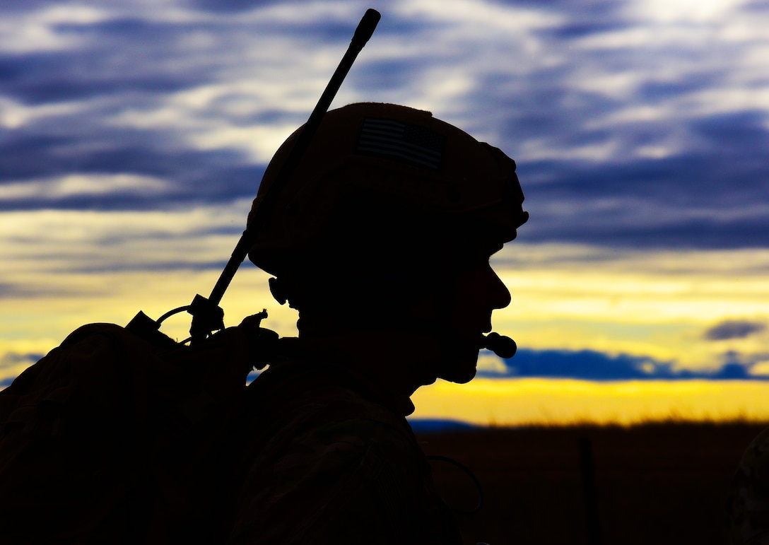 A joint terminal attack controller assigned to the 5th Air Support Operations Squadron, Joint Base Lewis-McChord, Wash., performs a radio check before a B-1 bomber flyby near Belle Fourche, S.D., Nov. 16, 2016. The fly-by was part of a show-of-force before a rescue helicopter could proceed to the area. (U.S. Air Force photo by Airman 1st Class James L. Miller)