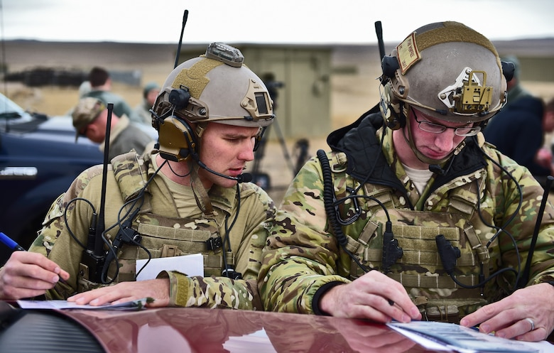 Airman 1st Class Ethan Gossett and Senior Airman Ryan Winfree, joint terminal attack controllers assigned to the 5th Air Support Operations Squadron, Joint Base Lewis-McChord, Wash., double check their numbers before a B-1 flyover near Belle Fourche, S.D., Nov. 16, 2016. JTAC members direct the action of combat aircraft engaged in close-air-support and other offensive air operations from a forward position. (U.S. Air Force photo by Airman 1st Class James L. Miller)
