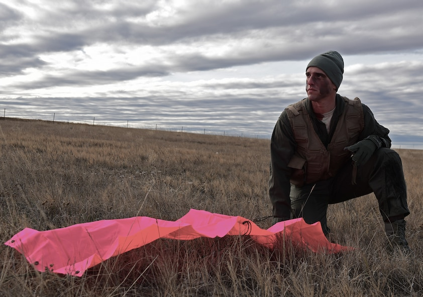 A pilot assigned to the 28th Bomb Wing, Ellsworth Air Force Base, S.D., waits for rescue at a simulated crash site near Belle Fourche, S.D., Nov. 16, 2016. The bright tarp laid out on the ground is a way to attract the attention of rescue pilots without drawing unwanted attention from hostile ground forces. (U.S. Air Force photo by Airman 1st Class James L. Miller)