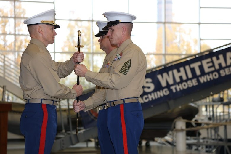 The 9th Marine Corps District commanding officer, Col. Jason Morris, and Sgt. Maj. John S. Hawes, pass the noncommissioned officer sword during the relief and appointment ceremony aboard Naval Station Great Lakes, Ill., on Nov. 18, 2016. The emblematic passing of the sword of office signifies the transfer of sacred trust from one sergeant major to another. (U.S. Marine Corps photo by Cpl. Zachery Martin/Released)