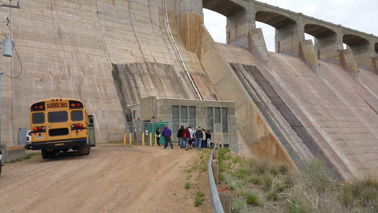 CONCHAS DAM, N.M. – For many years, the big end-of-the-year field trip for the local fifth grade class (including the parents) in Tucumcari, N.M., is a tour of the dam. Park rangers go to the school beforehand and give a history presentation with photos where the students learn why and how the dam was built and how it works. For this event even the maintenance personnel get involved! Here, maintenance worker Steve Chacon explains to the group what the stilling basin of the dam is, May 17, 2016. Photo by Taylor Atwood. This was a 2016 Photo Drive entry.