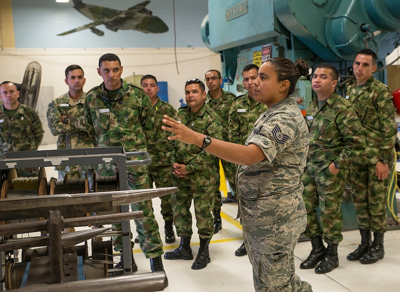 Tech. Sgt. Stephanie Rymers, 433rd Maintenance Squadron sheet metal mechanic, explains the sheet metal fabrication process to Inter-American Air Forces Academy students Nov. 17, 2016 at Joint Base San Antonio-Lackland, Texas. The students also toured a C-5M Galaxy and the engine and structural shops at the 433rd Airlift Wing.  (U.S. Air Force photo by Benjamin Faske)