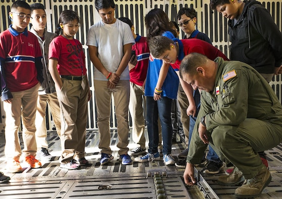 Master Sgt. Eric Mungia, 68th Airlift Squadron load master, shows students from Harmony Science Academy San Antonio the roller system that is used to move palletized cargo onto C-5M Super Galaxy aircraft Nov. 17, 2016 at Joint Base San Antonio-Lackland, Texas. The students also toured the engine, metal, and structural shops at the 433rd Airlift Wing.  (U.S. Air Force photo/Benjamin Faske)