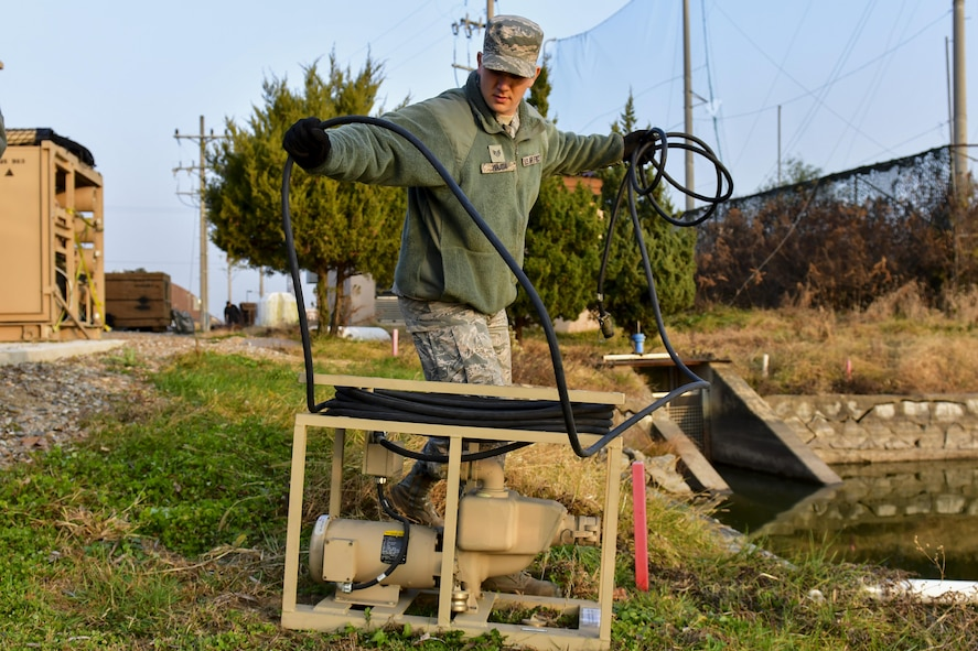 U.S. Air Force Staff Sgt. James Wajda, 51st Civil Engineer Squadron water fuels systems maintenance craftsman, sets up a raw water pump at Osan Air Base, Republic of Korea, Nov. 17, 2016. The pump is used to push water into a filtration system to generate large quantities of drinkable water for the base population. (U.S. Air Force photo by Senior Airman Victor J. Caputo)
