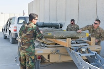 Staff Sgt. Aaron Clover and Tech. Sgt. Aaron Moore, Train, Advise, Assist Command-Air (TAAC-Air) munitions air advisors assist a member of the Afghan Air Force load Mark-81 bombs onto a trailer at Mazar-E-Sharif, Afghanistan, Nov. 18, 2016. The bombs were offloaded from an A-29 Super Tucano. (U.S. Air Force photo by Tech. Sgt. Christopher Holmes)