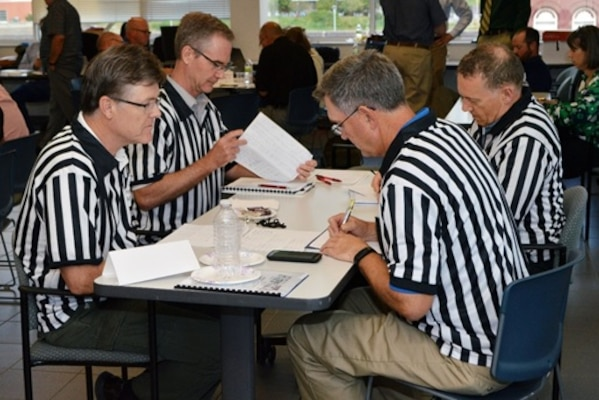 Referees deliberating teams' scores based on the appropriateness of adaptation options; consideration of the ecological, economic and societal impacts; and on innovation.