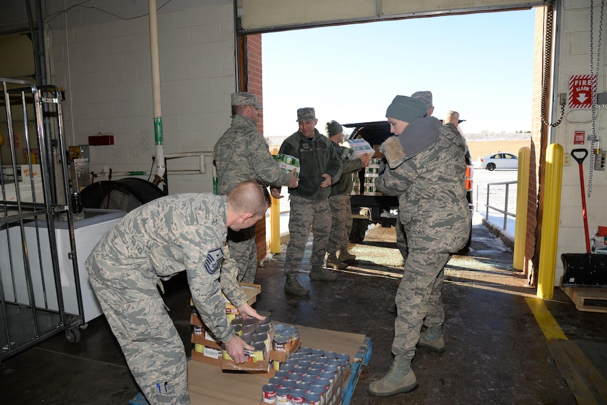 90th Missile Wing first sergeants pack up Thanksgiving basket food items in the commissary warehouse at F.E. Warren Air Force Base, Wyo., Nov. 18, 2016. Also known as OPERATION WARMHEART to the public, many of the funds are provided through community members and the Combined Federal Campaign charity (code 19015). The baskets will be delivered to junior-ranking Airmen, selected by their chain of command, to ensure their families are able to enjoy a Thanksgiving meal for the holiday. (U.S. Photo by 2d Lt. Nikita Thorpe)