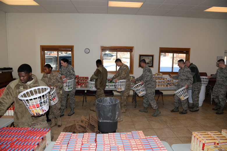 First sergeant council volunteers form an assembly line to quickly and efficiently build Thanksgiving baskets in the High Plains chapel at F.E. Warren Air Force Base, Wyo., Nov. 18, 2016.  Volunteers put together 125 baskets equipped with everything needed to provide a complete meal, including a gift card to purchase a turkey. The baskets will be delivered to junior-ranking Airmen, selected by their chain of command, to ensure their families are able to enjoy a Thanksgiving meal for the holiday. (U.S. Photo by 2d Lt. Nikita Thorpe)