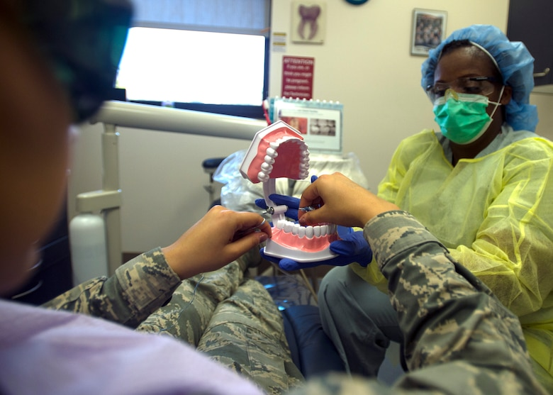 Staff Sgt. Sandra Denson, 59th Dental Group dental assistant, watches a patient demonstrate on 'how to floss' the correct way at the Dunn Dental Clinic on Joint Base San Antonio-Lackland, Texas, Nov. 18. Dental health professionals recommend flossing at least once a day to prevent calcium buildup and cavities. (U.S. Air Force photo/Staff Sgt. Kevin Iinuma)