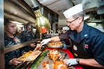 Navy Capt. Mike Wettlaufer, commanding officer aboard the aircraft carrier USS John C. Stennis (CVN 74), serves turkey during a Thanksgiving meal Nov. 26, 2015. DLA Troop Support's Subsistence supply chain provides service members around the world a taste of home for Thanksgiving every year.