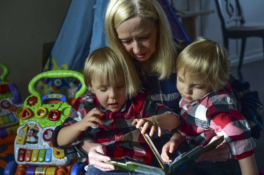 Robbie Wren-a Aswegan reads a book to her grandsons during their third birthday party Nov. 2, 2016, at the Douglas family home in Colorado Springs, Colo. The twins, born premature at 23 weeks, 17 weeks earlier than normal have experienced various physical trials along their journey through life. (U.S. Air Force photo by Airman 1st Class Gabrielle Spradling/Released)