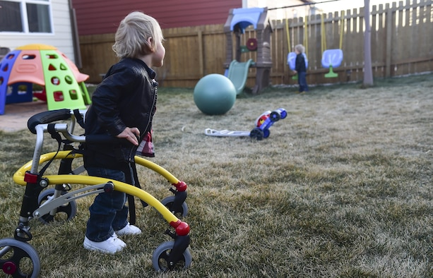 Dean Fredric Douglas watches his twin brother, Luke James Douglas, play on a swing set Nov. 2, 2016, at their family home in Colorado Springs, Colo. Both Dean and Luke suffered complications during a premature birth at 23 weeks, however, Dean is much more limited because he had several brain bleeds that caused him to have cerebral palsy in his legs. (U.S. Air Force photo by Airman 1st Class Gabrielle Spradling/Released)