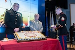Oldest Marine Sgt. Gary A. Rodgers passes cake to Sgt. Austin Reed, the youngest Marine during the cake cutting ceremony that serves as the hallmark of the Marine Corps birthday ceremony.
