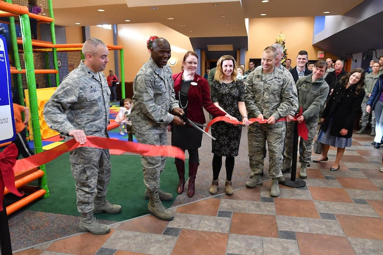 Leaders from the 319th Air Base Wing reopen the Community Activities Center on Grand Forks Air Force Base, N.D., Nov. 21, 2016. The CAC serves as a community commons, which now includes an indoor play center, game area and auditorium. (U.S. Air Force photo by Airman 1st Class Elijaih Tiggs)