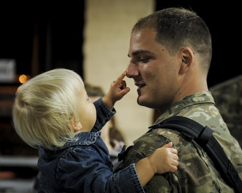 Senior Airman Ryan Randolph, a hydraulic specialist with the 1st Special Operations Maintenance Squadron, holds his child during Operation Homecoming at Hurlburt Field, Fla., Nov. 10, 2016. Randolph, along with 107 other Air Commandos, returned from a four-month deployment. (U.S. Air Force photo by Airman Dennis Spain)