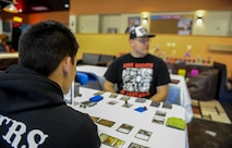 Airman 1st Class Nathan Harris, a personnel specialist with the 1st Special Operations Force Support Squadron, and Airman 1st Class William Cornwell, an aircraft metals technician with the 1st Special Operations Maintenance Squadron, participate in a trading card tournament at the Commando Con event held at the Landing Zone Community Center on Hurlburt Field, Fla., Nov. 19, 2016. Commando Con is based off comic conventions where like-minded individuals immerse themselves in a fantasy world by dressing up as their favorite fictional characters. (U.S. Air Force photo by Airman 1st Class Isaac O. Guest IV)