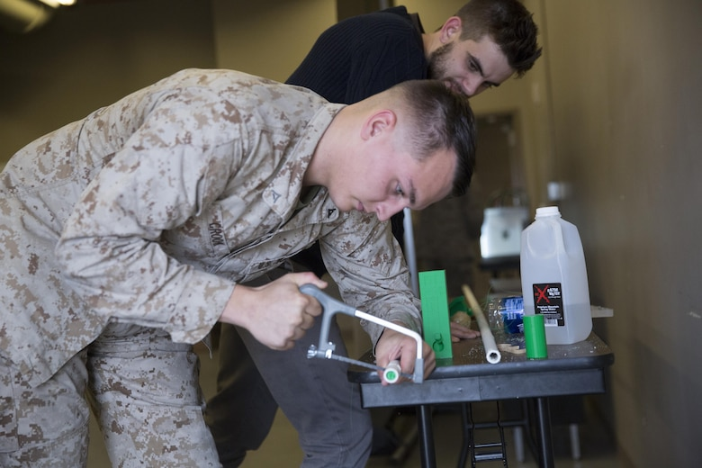 Lance Cpl. Tyler Crook, machinist, Combat Logistics Company 13, saws PVC piping during a 3D printing class aboard Marine Corps Air Ground Combat Center, Twentynine Palms, Calif., Nov. 16, 2016. Over the three-day course, Marines were challenged to manufacture innovative solutions for the problems presented to them using 3D printing innovation. (Official Marine Corps photo by Cpl. Medina Ayala-Lo/Released)