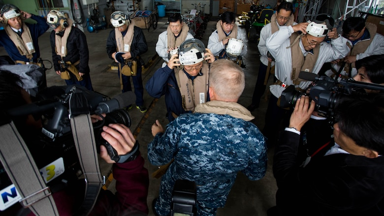 Navy Capt. Ed Thomson, commander of Amphibious Squadron 11; Mr. Norio Tomonaga, the Mayor of Sasebo City, Japan; and the Assemblymen of Defense for Sasebo City put on flight equipment before boarding a MV-22B Osprey tiltrotor aircraft at Sasebo, Nagasaki, Japan, Nov. 18, 2016. The aircraft flew from the island of Okinawa, conducted simulated humanitarian aid with the Japan Maritime Self-Defense Force at multiple locations and was refueled by JMSDF personnel before returning to Okinawa.