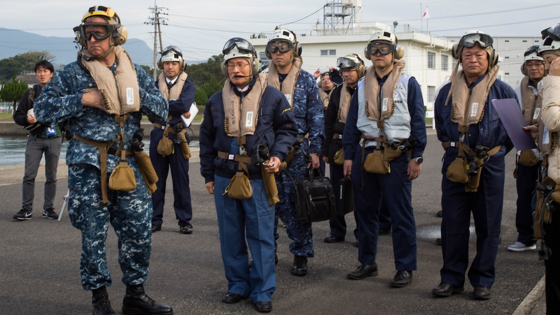 Navy Capt. Ed Thomson, commander of Amphibious Squadron 11; Mr. Norio Tomonaga, the Mayor of Sasebo City, Japan; and the Assemblymen of Defense for Sasebo City stand-by to board a MV-22B Osprey tiltrotor aircraft at Sasebo, Nagasaki, Japan, Nov. 18, 2016. The aircraft flew from the island of Okinawa, conducted simulated humanitarian aid with the Japan Maritime Self-Defense Force at multiple locations and was refueled by JMSDF personnel before returning to Okinawa.