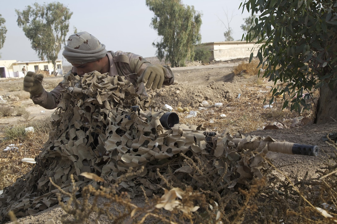Iraqi soldiers, acting as a fire team, utilize their environment to camouflage themselves during stalking training at Camp Taji, Iraq, Nov. 16, 2016. This training is critical to enabling the Iraqi security forces to counter Da'esh as they work to regain territory from the terrorist group. (U.S. Army photo by Spc. Craig Jensen)