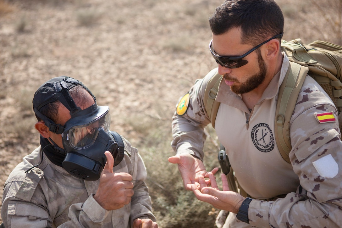 A Spanish trainer works with an Iraqi security forces soldier during a training session on the proper use of protective masks at the Besmaya Range Complex, Iraq, Nov. 13, 2016. The Spanish army provides training at Camp Besmaya, one of four Combined Joint Task Force – Operation Inherent Resolve building partner capacity locations dedicated to training Iraqi security forces. (U.S. Army photo by Sgt. Josephine Carlson)