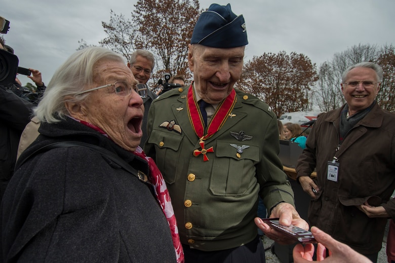 Retired U.S. Air Force Col. Gail Halvorsen, a C-52 Skymaster pilot also known as the Candy Bomber, prepares to present a chocolate bar to Gisela Rainare, a former civilian employee at the former Frankfurt an Main Air Base, Germany, before the reopening ceremony of the Berlin Airlift Memorial outside Frankfurt International Airport, Germany, Nov. 22, 2016. Halvorsen and his fellow pilots dropped 23 tons of candy with makeshift parachutes from his C-54 as part of the Berlin Airlift, which delivered more than two million tons of food to the blockaded citizens of West Berlin between June 1948 and September 1949. (U.S. Air Force photo by Staff Sgt. Joe W. McFadden)