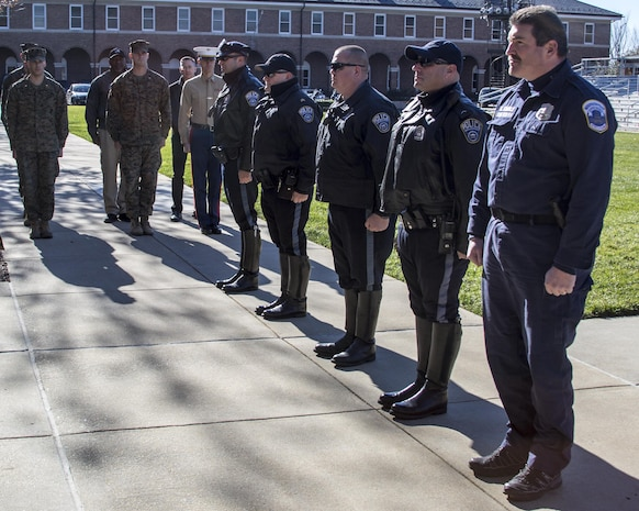 U.S. Marines with Guard Company, Marine Barracks Washington, D.C., and members of the Arlington County Police Department and D.C. Metropolitan Police Department stand at attention while citations are read for the officers during an award ceremony at the Barracks, Nov. 21, 2016. These officers were rewarded for supporting the Barracks Marines in protecting the thousands of guests, both civilian and military, that attend our annual parades.(Official Marine Corps photo by Lance Cpl. Robert Knapp/Released)