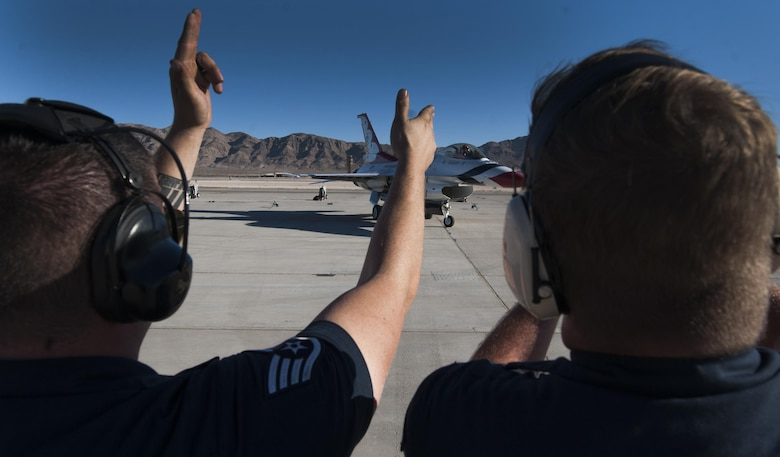 U.S. Air Force Thunderbird Air Demonstration Squadron crew chiefs cheer on a Thunderbird jet as it taxis down the runway during Aviation Nation on Nellis Air Force Base, Nev., Nov. 11, 2016. The Thunderbirds showcase the skill and precision of the aviators, maintenance and support Airmen who deploy to defend the nation and its allies. (U.S. Air Force photo by Airman 1st Class Kevin Tanenbaum/Released)