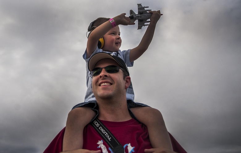 A young child sits on his father's shoulders during the U.S. Air Force Thunderbirds Air Demonstration Squadron aerial performance at the Aviation Nation air show on Nellis Air Force Base, Nev., Nov. 12, 2016. This event marked the end of the air show season for the U.S. Air Force Air Demonstration Squadron, the Thunderbirds. (U.S. Air Force photo by Airman 1st Class Kevin Tanenbaum/Released)