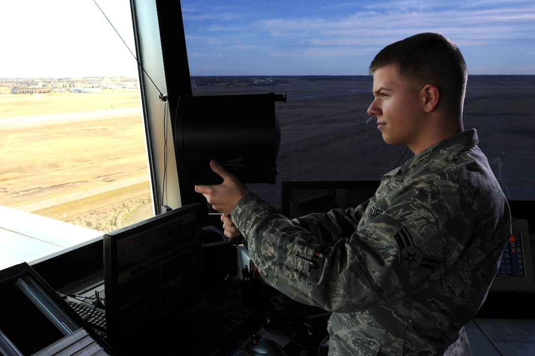 Airman 1st Class Christopher Quesenberry, 5th Operations Support Squadron air traffic controller, uses a light gun from the control tower at Minot Air Force Base, N.D., Nov. 15, 2016. Light guns are used to communicate with or direct aircraft in the case of radio failure. (U.S. Air Force photo/Senior Airman Kristoffer Kaubisch)