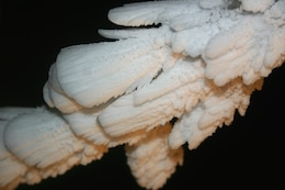 Rime ice forms grows in feather-like crystals (upper panel) from supercooled cloud droplets which freeze quickly, trapping air.