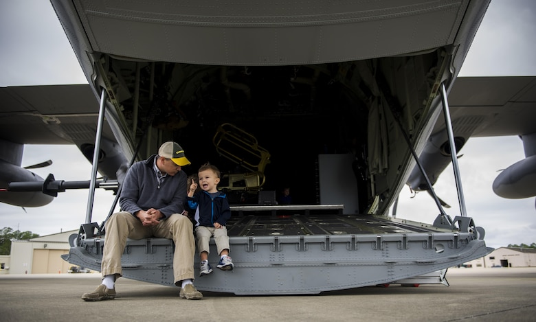 An Air Commando and his son sit on the back of an AC-130J Ghostrider gunship during a Spouses Flight tour at Hurlburt Field, Fla., Nov. 19, 2016. Before the flights began, spouse's toured static displays of different aircraft to get a firsthand look at capabilities of the1st Special Operations Wing. (U.S. Air Force photo by Airman 1st Class Isaac O. Guest IV)