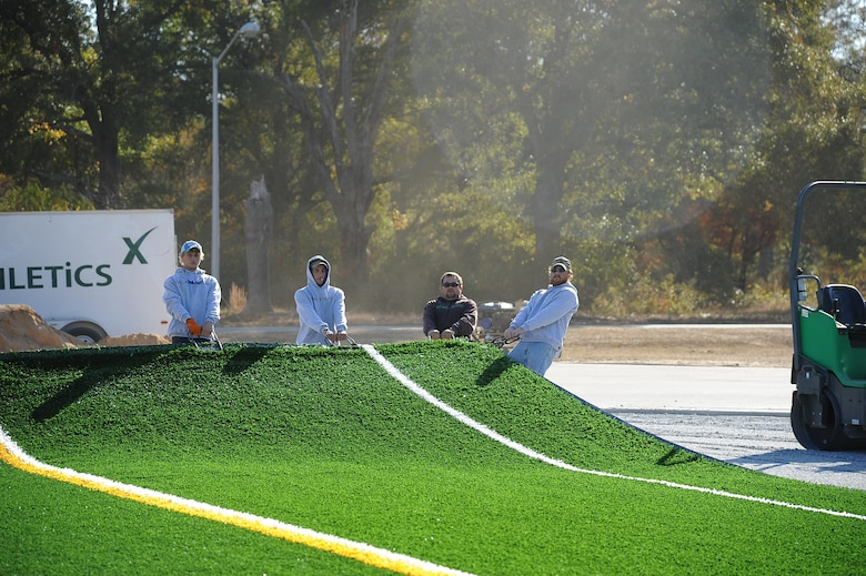 Contractors lay new turf at the Robins Fitness Center's track field across from the center. The entire area is being reconstructed and is scheduled to be complete around the beginning of the new year. (U.S. Air Force photo by Misuzu Allen)