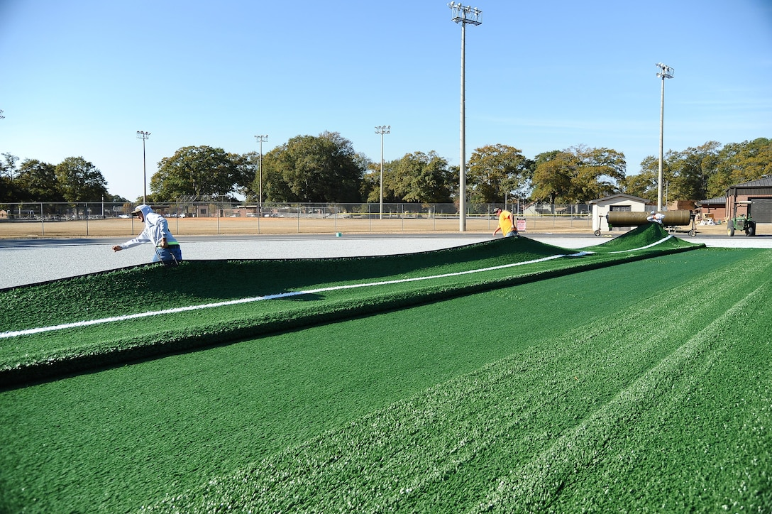 Contractors lay new turf at the base track across from the Fitness Center. The entire area is being reconstructed and is scheduled to be complete around the beginning of the new year. (U.S. Air Force photo by Misuzu Allen)