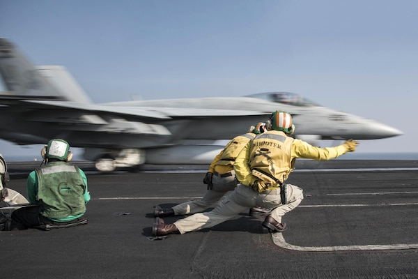 Navy Lt. Paul Dauffenbach, center foreground, and Lt. Charles Kreuz signal to an F/A-18E Super Hornet as it launches from the flight deck of the aircraft carrier USS Dwight D. Eisenhower in the Persian Gulf, Nov. 17, 2016. The Ike and its carrier strike group are supporting Operation Inherent Resolve and theater security cooperation efforts in the U.S. 5th Fleet area of operations. Navy photo by Petty Officer 3rd Class Anderson W. Branch