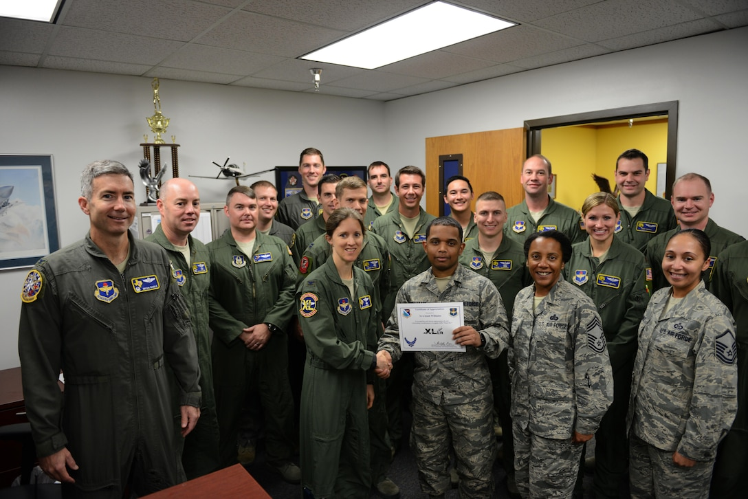 "Senior Airman Isiah Williams, 85th Flying Training Squadron administrative journeyman (front center), accepts the ""XLer of the Week"" award from Col. Michelle Pryor (front left), 47th Flying Training Wing vice commander, and Chief Master Sgt. Erica Shipp (front right), 47th Mission Support Group superintendent, on Laughlin Air Force Base, Texas, Nov. 16, 2016. The XLer is a weekly award chosen by wing leadership and is presented to those who consistently make outstanding contributions to their unit and Laughlin. (U.S. Air Force photo/Airman 1st Class Benjamin N. Valmoja)"