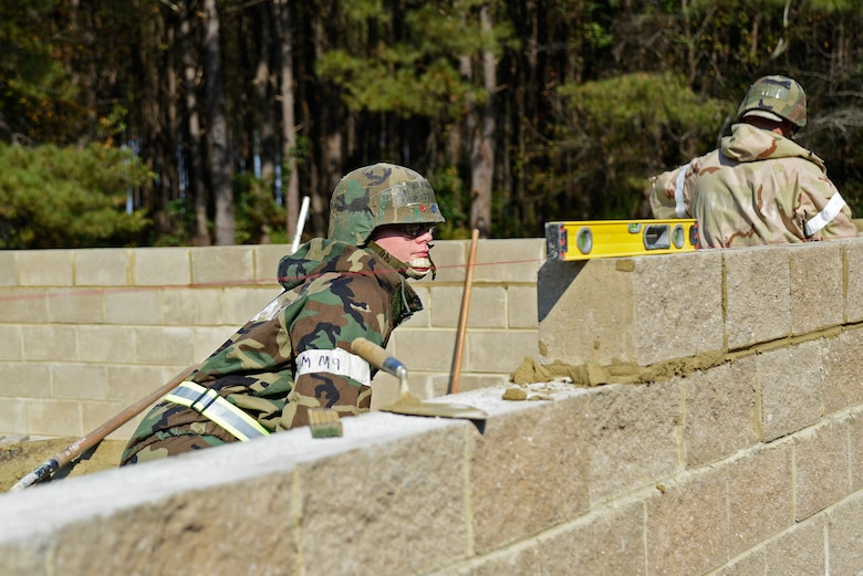 U.S. Air Force Airman 1st Class Nathen Trevino, 20th Civil Engineer Squadron structural apprentice, ensures a brick is level at Shaw Air Force Base, S.C., Nov. 16, 2016. Airmen from the 20th CES built an alternate Unit Control Center facility during operational readiness exercise Weasel Victory 17-03. (U.S. Air Force photo by Airman 1st Class BrieAnna Stillman)