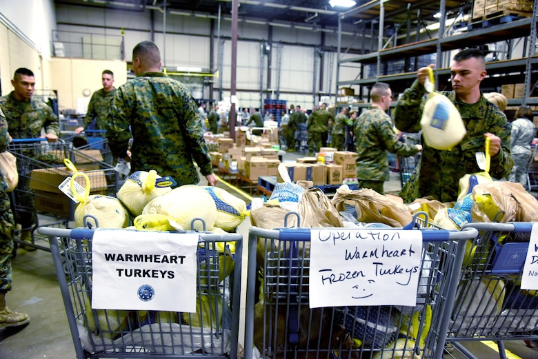 Marines load turkeys into carts at the start of Operation Warmheart inside the commissary on Goodfellow Air Force Base, Texas, Nov. 22, 2016. Volunteers filled care boxes with Thanksgiving food and gave them to service members for the holiday. (U.S. Air Force photo by Senior Airman Joshua Edwards/Released)