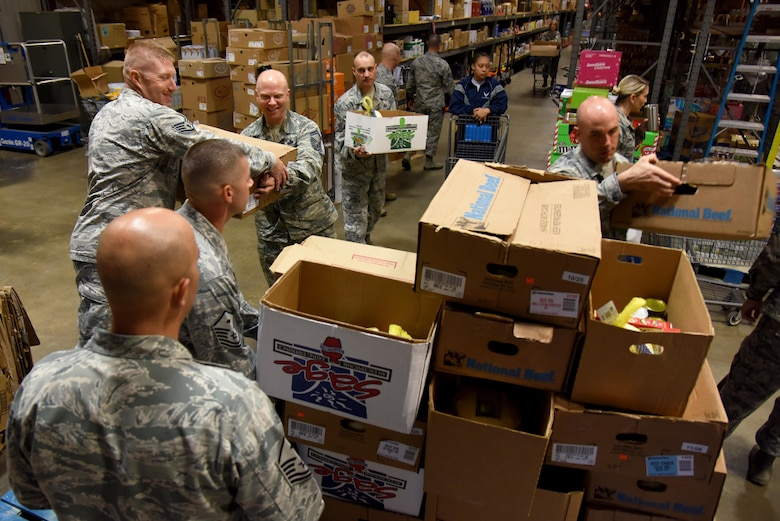 Airmen load filled boxes for Operation Warmheart onto a cart inside the commissary on Goodfellow Air Force Base, Texas, Nov. 22, 2016. The Goodfellow First Sergeant Association gave the boxes, which held a whole turkey and various non-perishable items, to 212 service members for Thanksgiving. (U.S. Air Force photo by Senior Airman Joshua Edwards/Released)