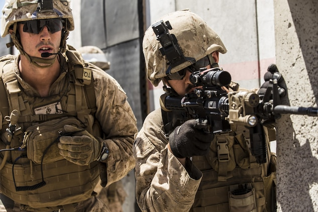 1st Lt. Austin Finnell (left) and Cpl. Jon Philips peer through an opening while conducting a raid during the 11th Marine Expeditionary Unit's Combined Arms Exercise at Marine Corps Air Ground Combat Center Twentynine Palms, Calif., June 12, 2016. A raid is an operation, usually small scale, involving a swift penetration of hostile territory to secure information, confuse the enemy, or to destroy his installations. MEUCAX is conducted to maintain a high level of combat readiness prior to the 11th MEU's Western Pacific 16-2 deployment later this year. Finnell is an infantry officer and Philips is a light armored vehicle repairer; both are with LAR Company, Battalion Landing Team 1st Bn., 4th Marines, 11th MEU. (U.S. Marine Corps photo by Lance Cpl. Zachery Laning/Released)
