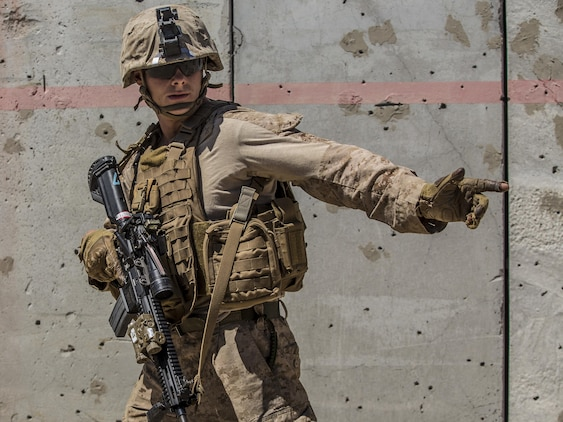 Lance Cpl. Michael Webster signals to his team while conducting a raid during the 11th Marine Expeditionary Unit's Combined Arms Exercise at Marine Corps Air Ground Combat Center Twentynine Palms, Calif., June 12, 2016. MEUCAX enables Battalion Landing Team 1st Battalion, 4th Marines to refine their offensive and defensive tactics at the company and battalion levels. This training enables the Marines to practice transitioning from an offensive attack to the defense position, both during day and night operations. The culminating event will involve a battalion ground offensive in coordination with Marine aviation close-air support. MEUCAX is conducted to maintain a high level of combat readiness prior to the MEU's Western Pacific 16-2 deployment later this year. Webster is a rifleman with LAR Company, Battalion Landing Team 1st Bn., 4th Marines, 11th MEU. (U.S. Marine Corps photo by Lance Cpl. Zachery Laning/Released)