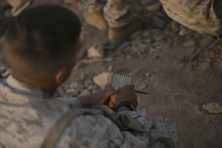 A Marine with 1st Battalion, 7th Marine Regiment, takes notes as the unit is briefed on the scheme of maneuver at Range 400 aboard Marine Corps Air Ground Combat Center, Twentynine Palms, Calif., prior to the unit's night time combined arms live-fire exercise Nov. 16, 2016. (Official Marine Corps photo by Cpl. Julio McGraw/Released)