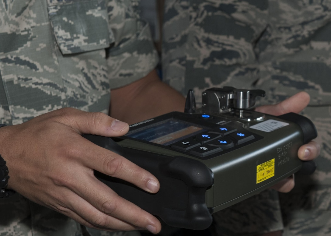 U.S. Air Force Senior Airman Gabriel Albano, 18th Aerospace Medicine Squadron bioenvironmental technician, discusses the different capabilities of a HazMatID Elite, a chemical identifier, during the Chemical, Biological, Radiological and Nuclear (CBRN) Exposition Nov. 17, 2016, at Kadena Air Base, Japan. The CBRN Exposition highlights the different equipment each branch of service utilizes. (U.S. Air Force photo by Senior Airman Lynette M. Rolen/Released)